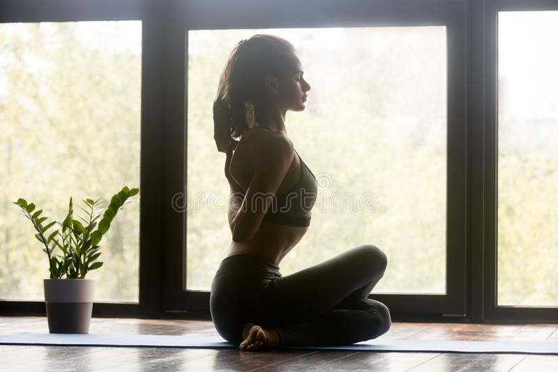 Young sporty woman Cow Face exercise, side view stock photography