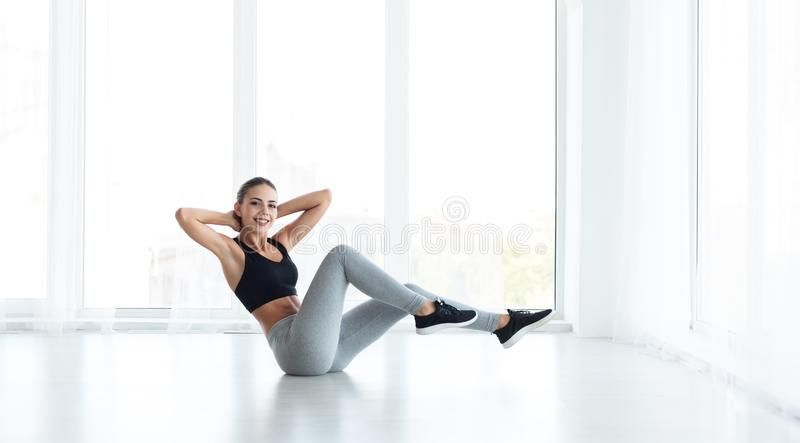 Young sporty woman doing crisscross exercise on floor royalty free stock photo