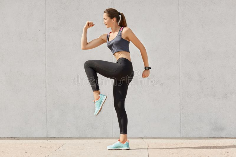 Young sporty woman doing exercise against gray background, dressed top, leggins, sneakers, has pony tail, raises legs, has intense. Workout, keeps fit, preapres stock photo