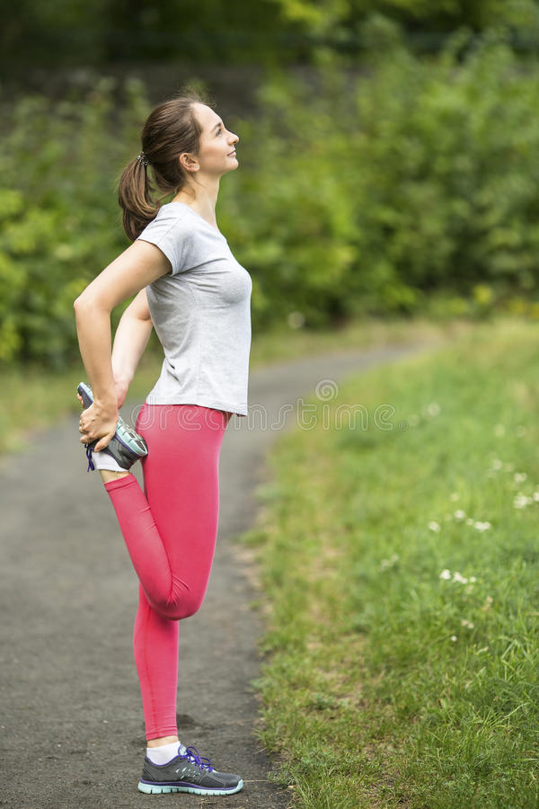 Young sporty woman doing exercise warm-up before Jogging in park in sunshine on beautiful summer day. stock images