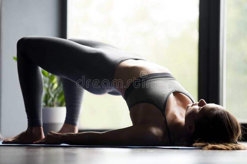 Young sporty woman doing Glute Bridge exercise stock photo