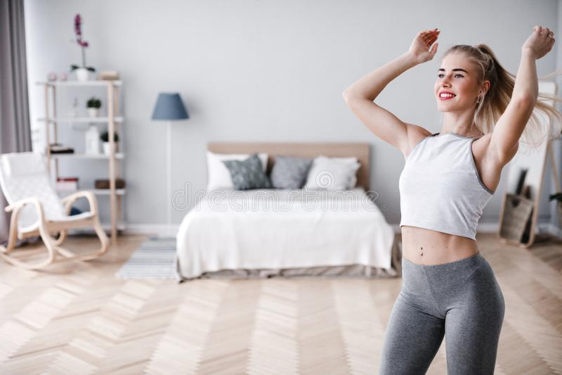 Young sporty woman doing morning exercise standing in living room stock photography