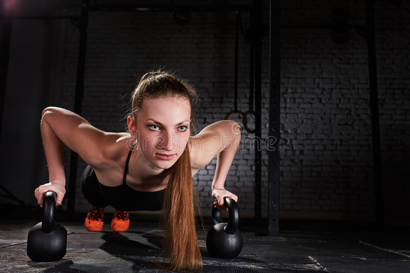 Young sporty woman doing push-ups exercise with kettlebell against brick wall. royalty free stock images