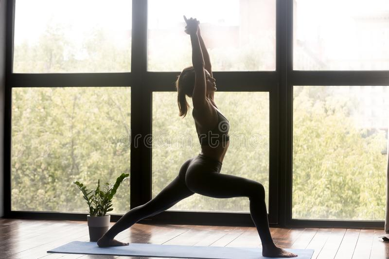 Young sporty woman doing Warrior one exercise royalty free stock image