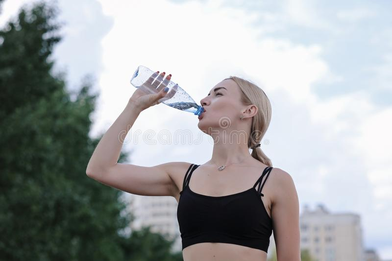 Young sporty woman drinking still water from a bottle. Fitness and lifestyle concept. Close up royalty free stock photos