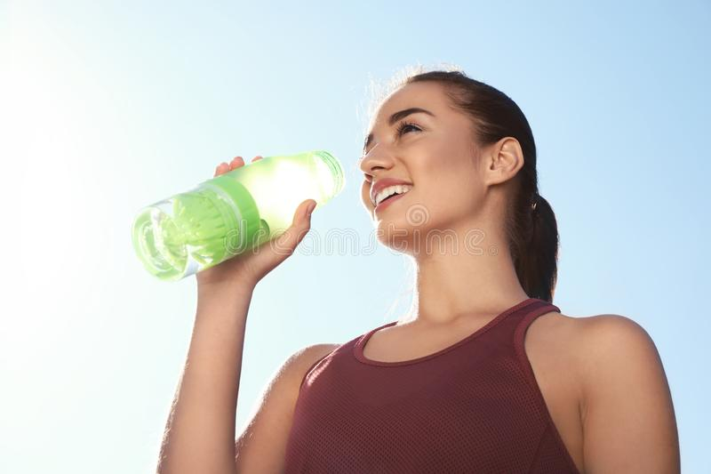 Young sporty woman drinking water from bottle against blue sky stock photo