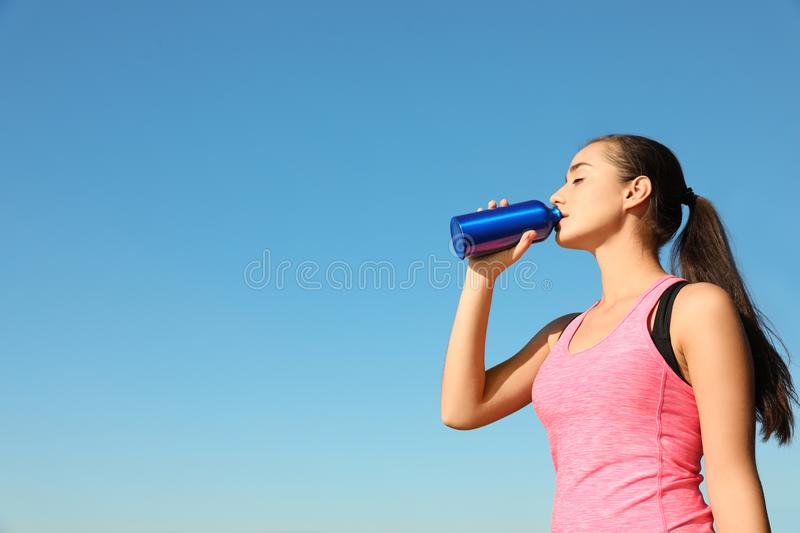 Young sporty woman drinking from water bottle outdoors on sunny day. Space for text stock image