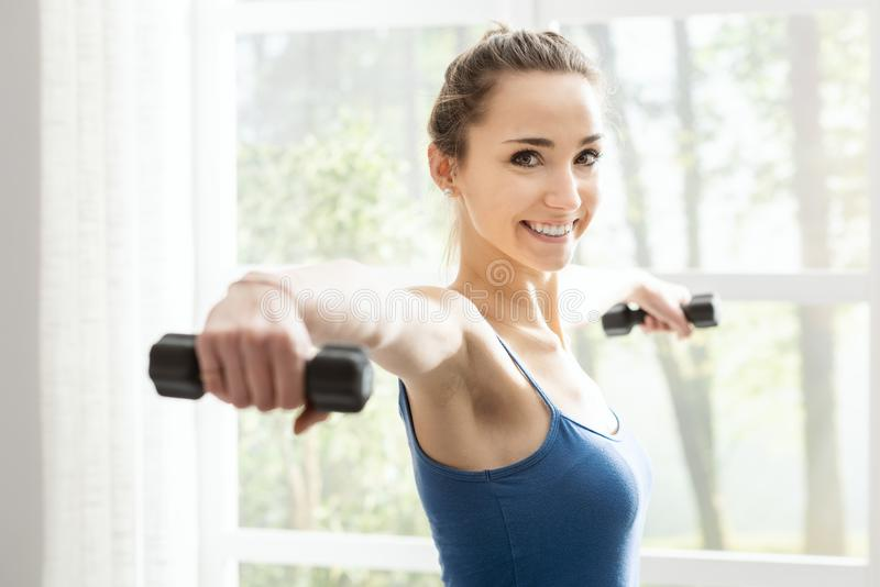 Young sporty woman exercising with dumbbells at home. Young smiling woman exercising at home next to a window, she is lifting dumbbells, fitness and sports royalty free stock image