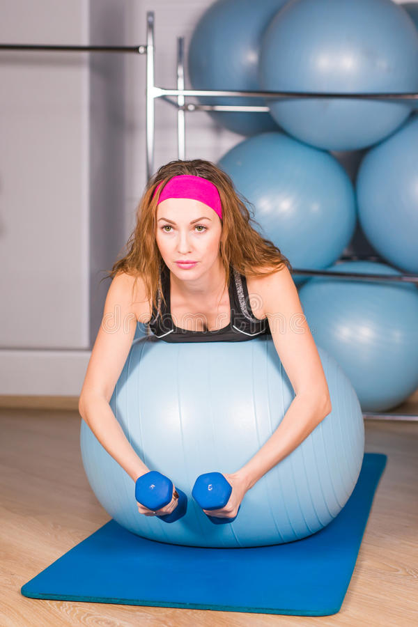 Young sporty woman in gym doing fitness exercice with blue ball.  stock photography