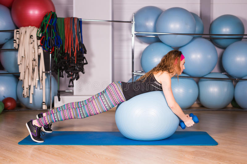 Young sporty woman in gym doing fitness exercice with blue ball.  stock photo