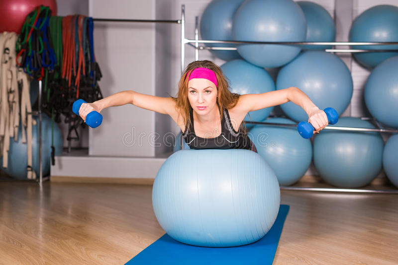 Young sporty woman in gym doing fitness exercice with blue ball.  royalty free stock images