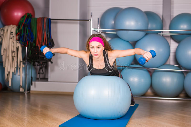 Young sporty woman in gym doing fitness exercice with blue ball.  royalty free stock photos