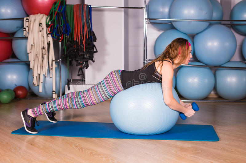 Young sporty woman in gym doing fitness exercice with blue ball.  royalty free stock photography