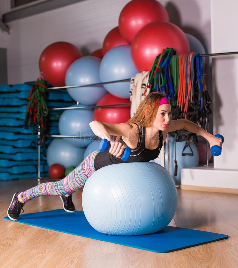 Young sporty woman in gym doing fitness exercice with blue ball.  stock images