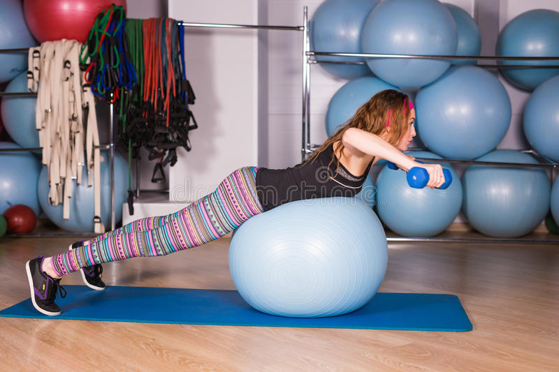Young sporty woman in gym doing fitness exercice with blue ball.  royalty free stock photo