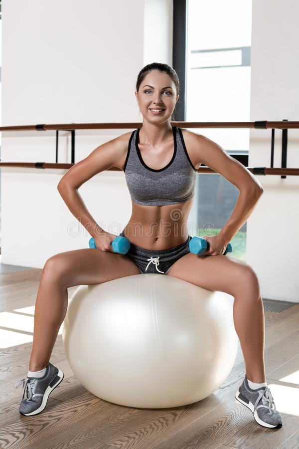 Young sporty woman in gym doing fitness exercise with white ball and dumbbells royalty free stock photo