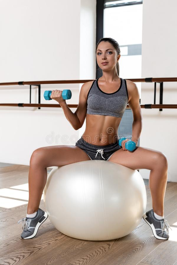 Young sporty woman in gym doing fitness exercise with white ball and dumbbells stock image