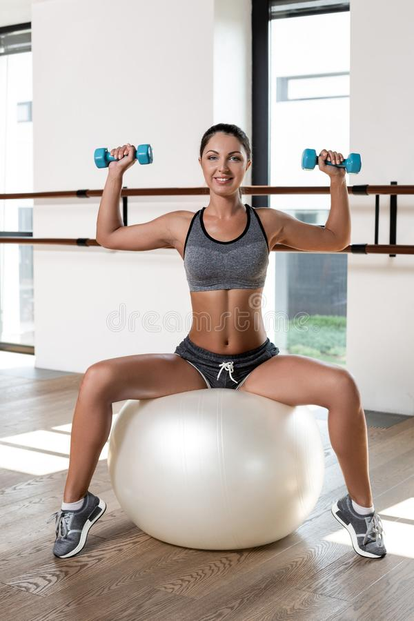 Young sporty woman in gym doing fitness exercise with white ball and dumbbells royalty free stock images