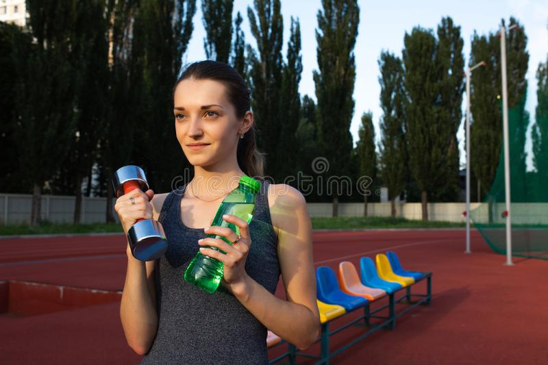 Young sporty woman holding the dumbbell and a water bottle at the stadium. Space for text stock images