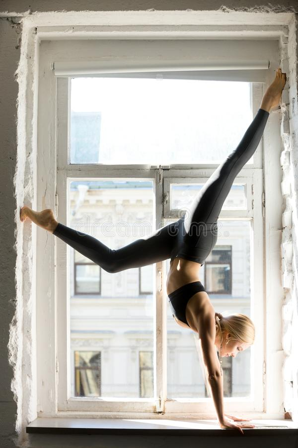 Free Young Sporty Woman In Downward Facing Tree Pose, Window Sill Stock Photo - 101255300