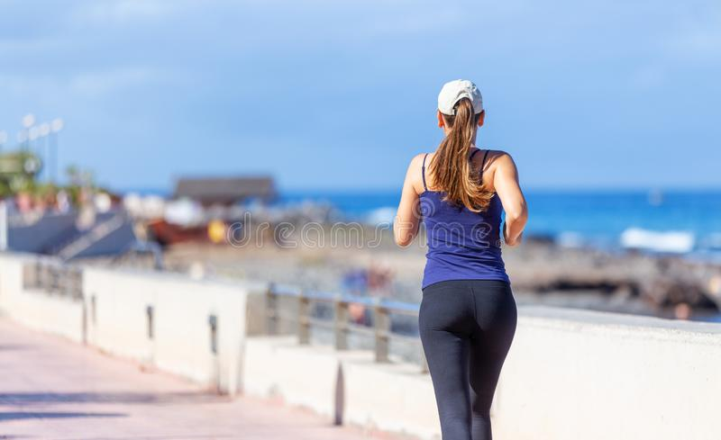 Young sporty woman jogging near the ocean royalty free stock image