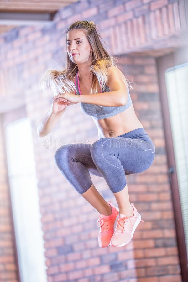 Young sporty woman jumping on mini trampoline in gym royalty free stock photography