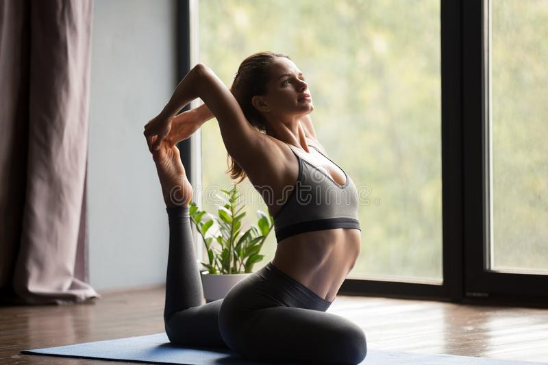 Young sporty woman in One Legged King Pigeon pose royalty free stock photo