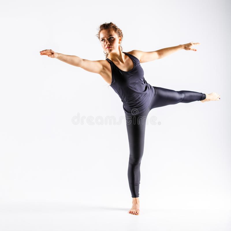 Young sporty woman performing warrior yoga pose royalty free stock image