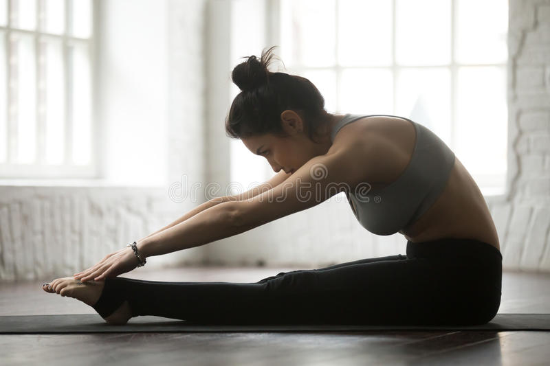 Young sporty woman practicing Pilates Spine Stretch Forward exer royalty free stock image