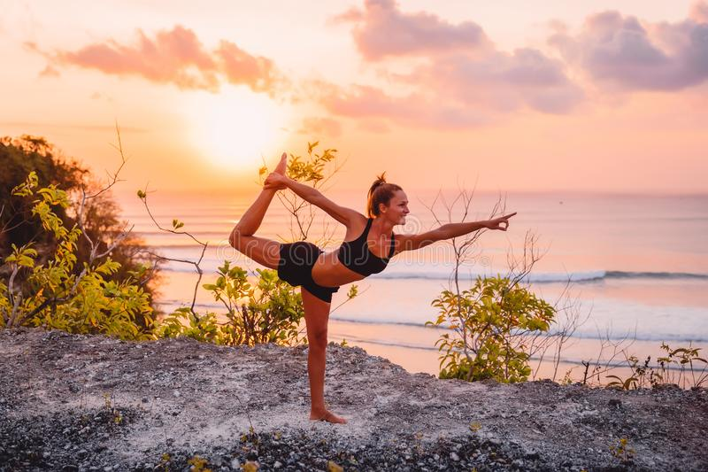 Young sporty woman practicing yoga at bright sunset time royalty free stock photography