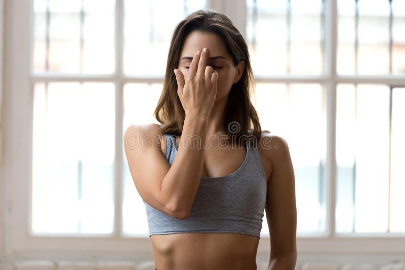 Young sporty woman practicing yoga, doing Alternate Nostril Brea. Thing exercise, nadi shodhana pranayama pose, working out, wearing sportswear, grey top, indoor stock photos