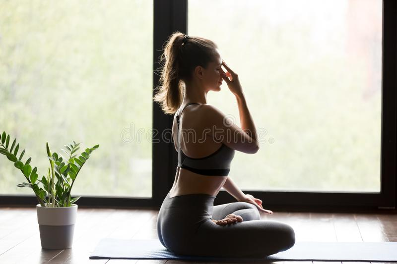 Young sporty woman practicing Alternate Nostril Breathing. Young sporty woman practicing yoga, doing Alternate Nostril Breathing exercise, nadi shodhana royalty free stock photos