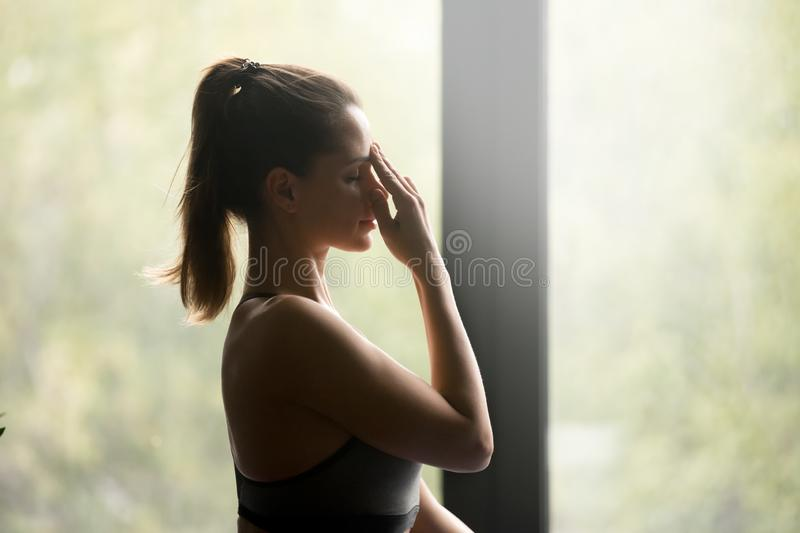 Young sporty woman doing Alternate Nostril Breathing. Young sporty woman practicing yoga, doing Alternate Nostril Breathing exercise, nadi shodhana pranayama royalty free stock image