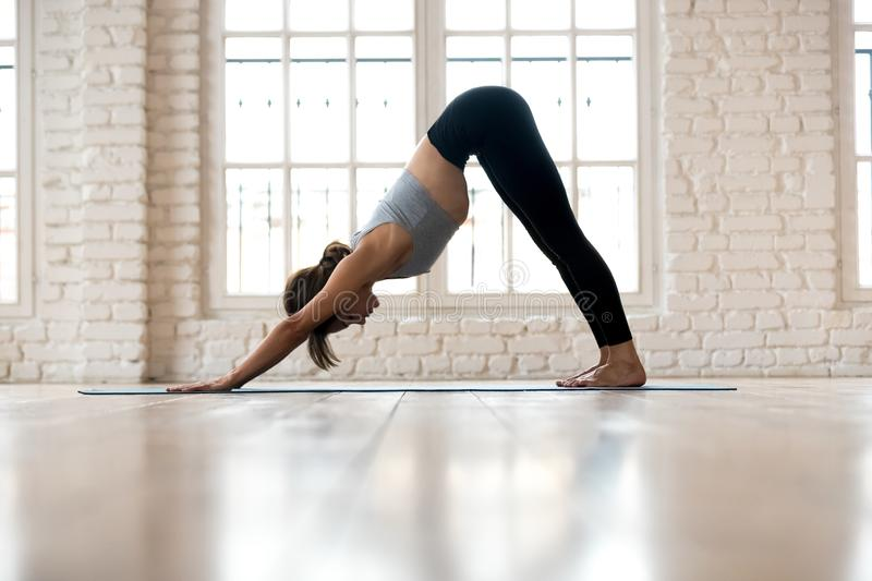 Young sporty woman practicing yoga, doing Downward facing dog ex. Ercise, adho mukha svanasana pose, working out, wearing sportswear, pants and top, indoor full stock photos