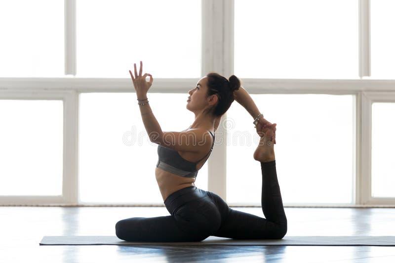 Young sporty woman practicing yoga, doing Eka Pada Rajakapotasan royalty free stock images