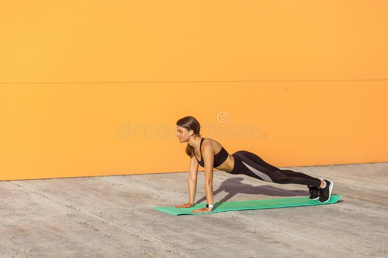 Young sporty woman practicing yoga, doing push ups or press ups exercise, phalankasana, plank pose, working out stock photos