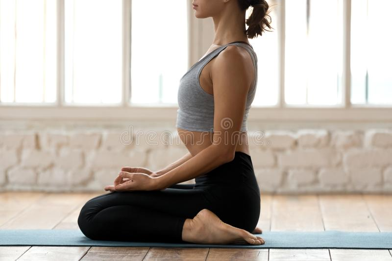 Young sporty woman practicing yoga, doing seiza exercise, close. Young sporty attractive woman practicing yoga, doing seiza exercise, vajrasana pose, working out royalty free stock image