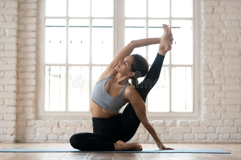 Young sporty woman practicing yoga, doing Surya Yantrasana exerc. Ise, Compass pose, working out, wearing sportswear, pants and top, indoor full length, white royalty free stock images
