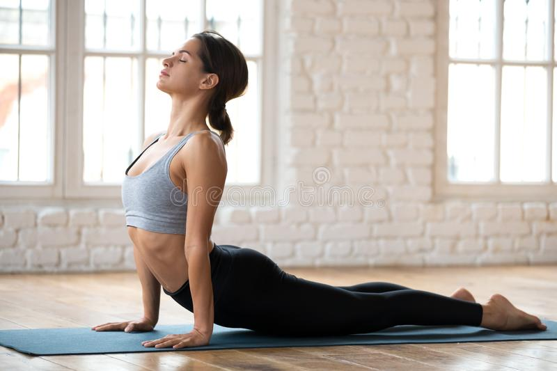 Young sporty woman practicing yoga, doing upward facing dog exer. Cise, Urdhva mukha shvanasana pose, working out, wearing sportswear, pants and top, indoor full royalty free stock photo