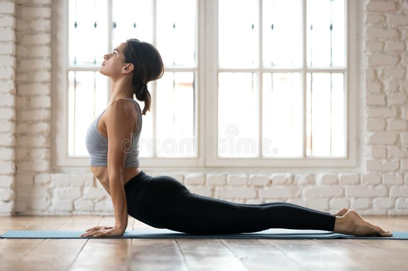 Young sporty woman practicing yoga, doing upward facing dog exer. Cise, Urdhva mukha shvanasana pose, working out, wearing sportswear, pants and top, indoor full royalty free stock photography