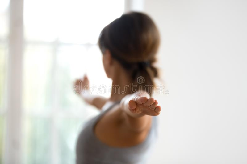 Young sporty woman practicing yoga, Warrior Two exercise, close. Young sporty attractive woman practicing yoga, doing Warrior II exercise, Virabhadrasana 2 pose stock photography