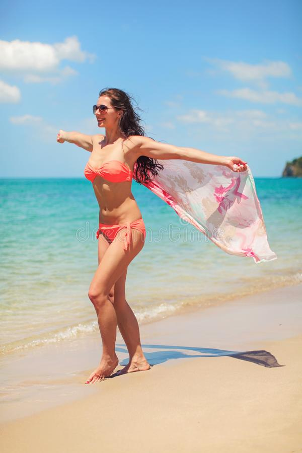 Young sporty woman in red bikini and sunglasses, stand on the beach, holds pink scarf waving in wind behind her. Turquoise sea and stock photo