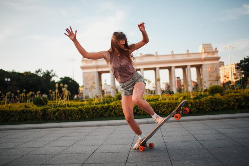 Young sporty woman riding on the longboard in the park. stock photography