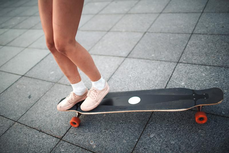 Young sporty woman riding on the longboard in the park. royalty free stock image