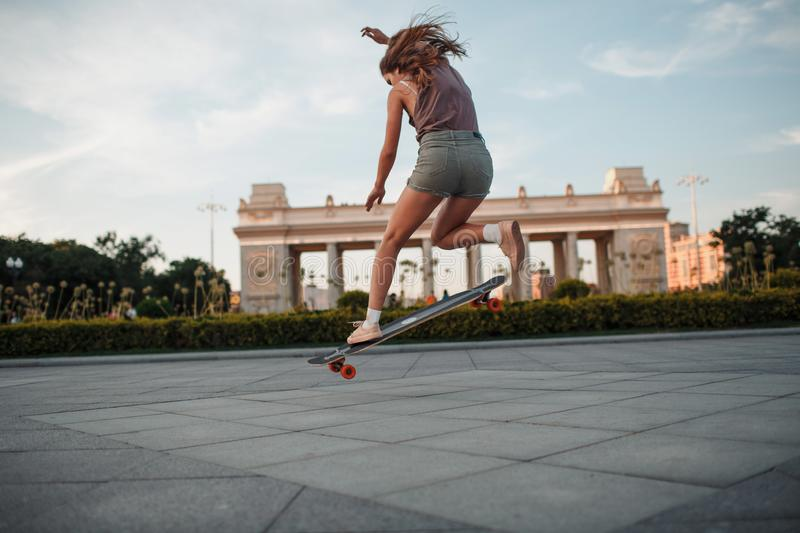 Young sporty woman riding on the longboard in the park. stock image