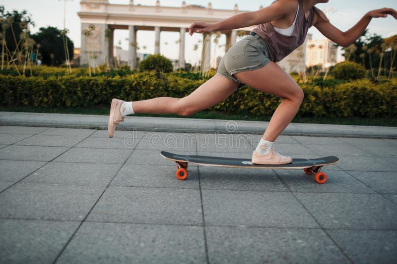 Young sporty woman riding on the longboard in the park. stock images