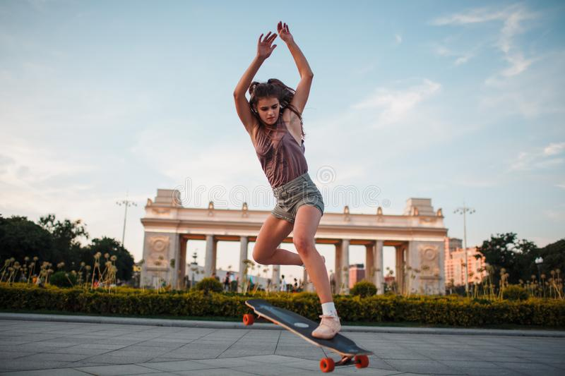 Young sporty woman riding on the longboard in the park. stock photo