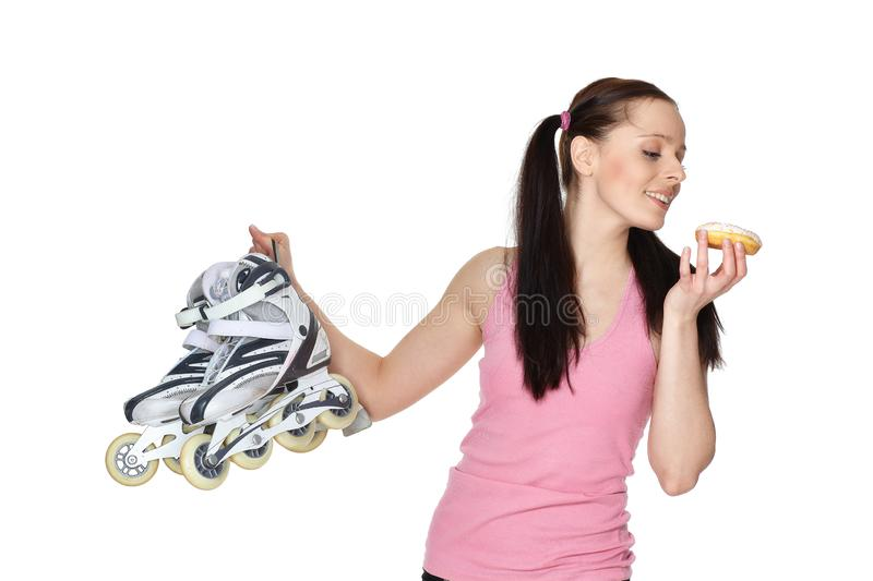 Young  sporty woman with rollerskates and donut royalty free stock image