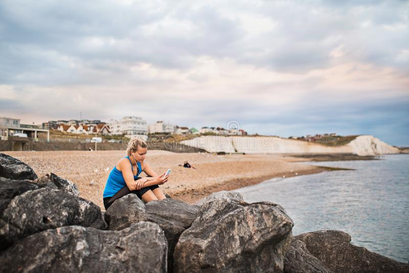 Young sporty woman runner with smartphone sitting on the beach outside, texting. royalty free stock photo