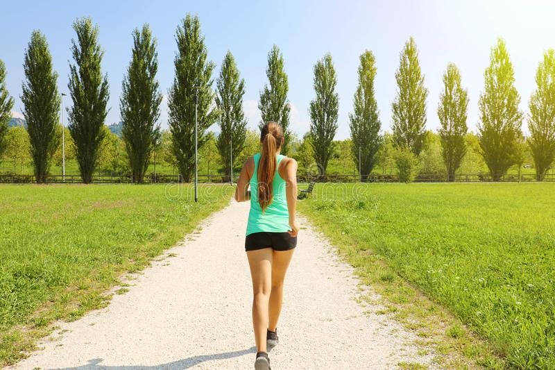 Young sporty woman running in park. Fitness girl jogging in park. Rear view of sporty girl running on pathway royalty free stock images
